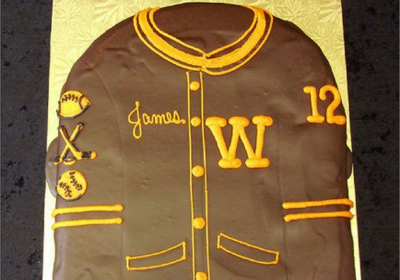 Personalize your bakery's graduation cakes for the individual by creating unique letter jacket cakes – complete with the graduate's name, number and sport insignias – like this example from Grandma's Bakery.
