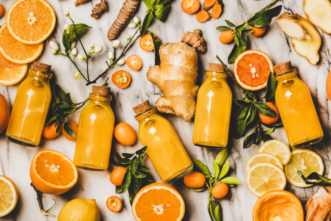 Flat-lay of fresh turmeric, ginger, citrus juice shot in glass bottles over marble background