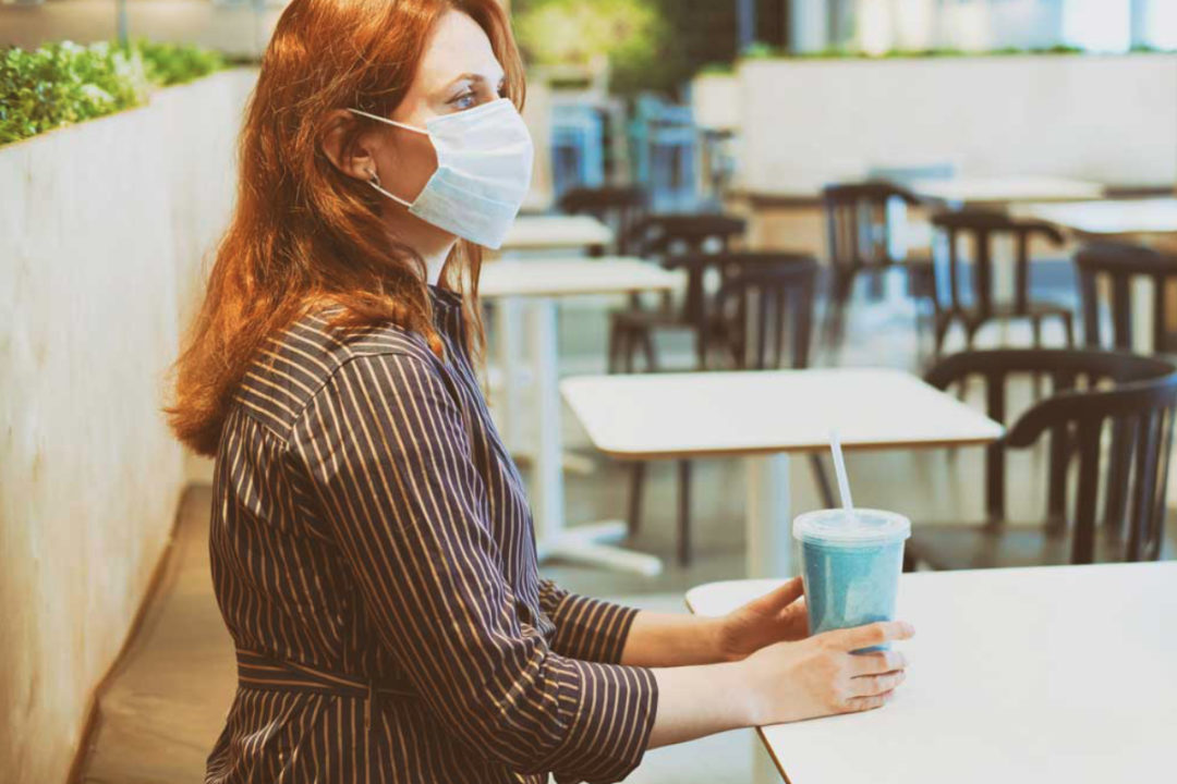 Woman wearing mask sitting inside restaurant with a drink