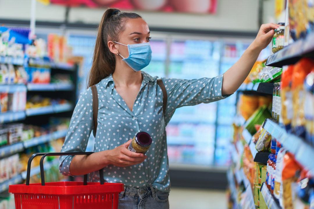 Woman wearing mask while grocery shopping during coronavirus pandemic