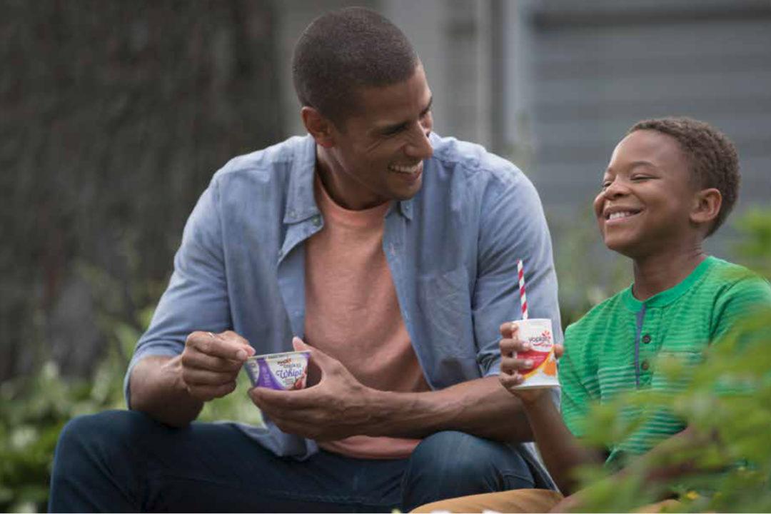 Father and son eating Yoplait yogurt