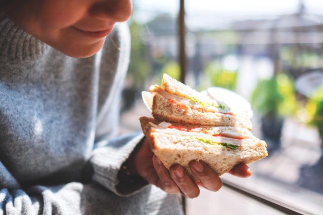 Woman eating whole grain wheat sandwich