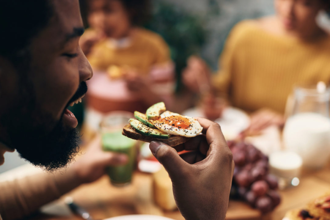 Black man eating avocado toast with his family at home