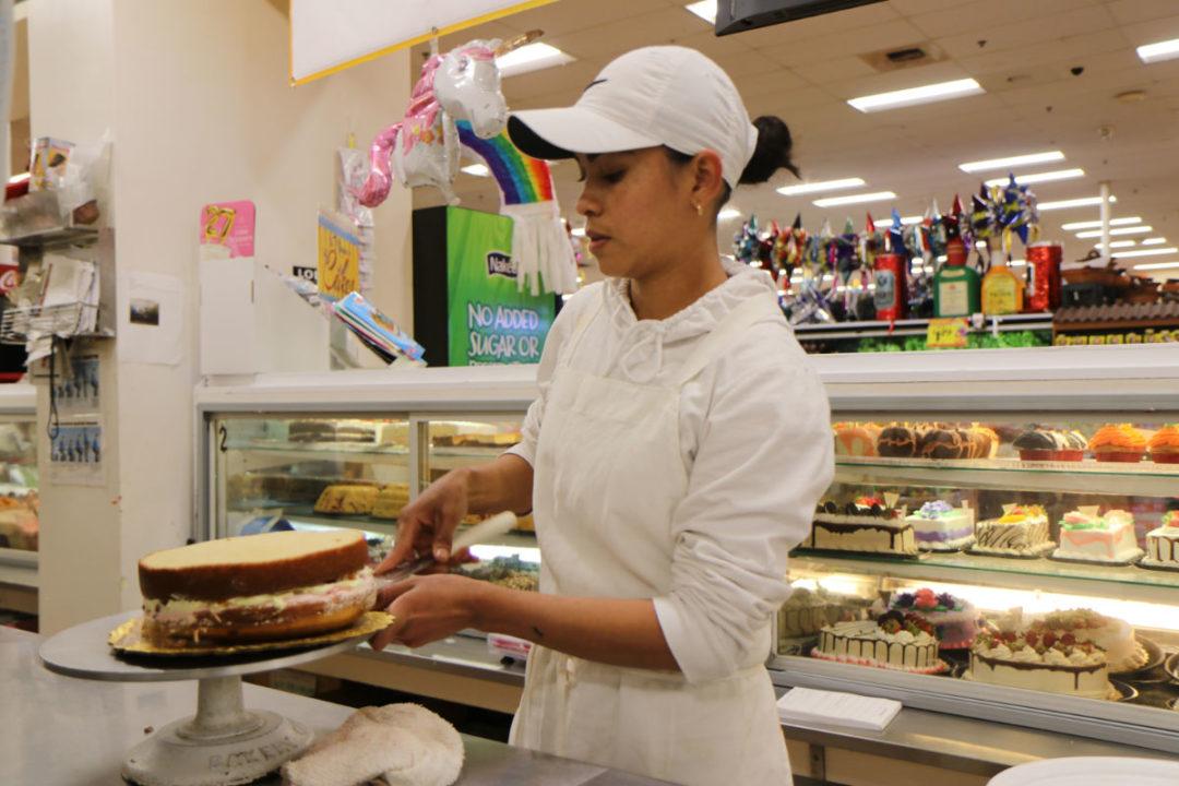 Bakery employee decorating cake